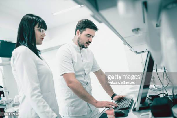 Dentist Showing Prosthetic Models On Computer To His Assistant