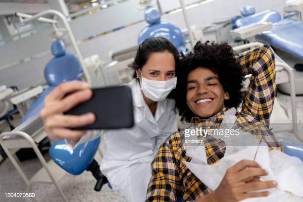 彼女の患者と自分撮りを取る歯科医 - 矯正歯科医 ストックフォトと画像