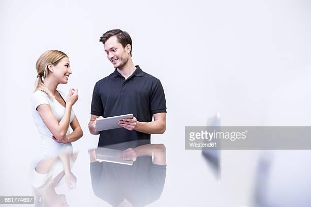 Dentist talking to patient , holding digital tablet