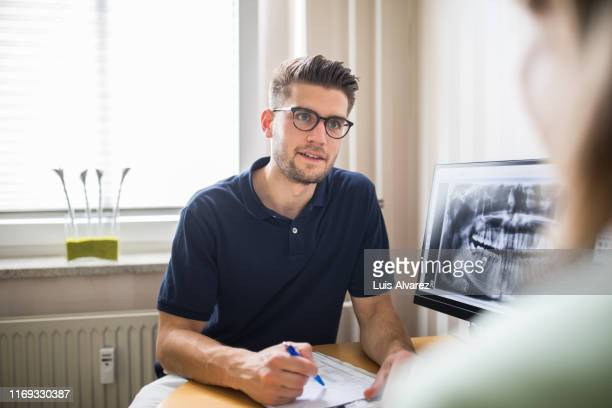 dentist talking with female patient in his clinic - clinic stock pictures, royalty-free photos & images