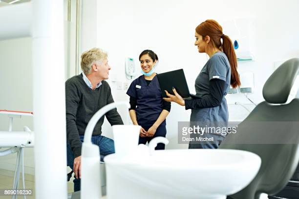 Dentist talking with two nurses