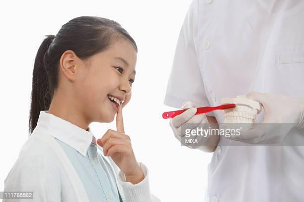 Dentist Teaching Girl Brushing Teeth