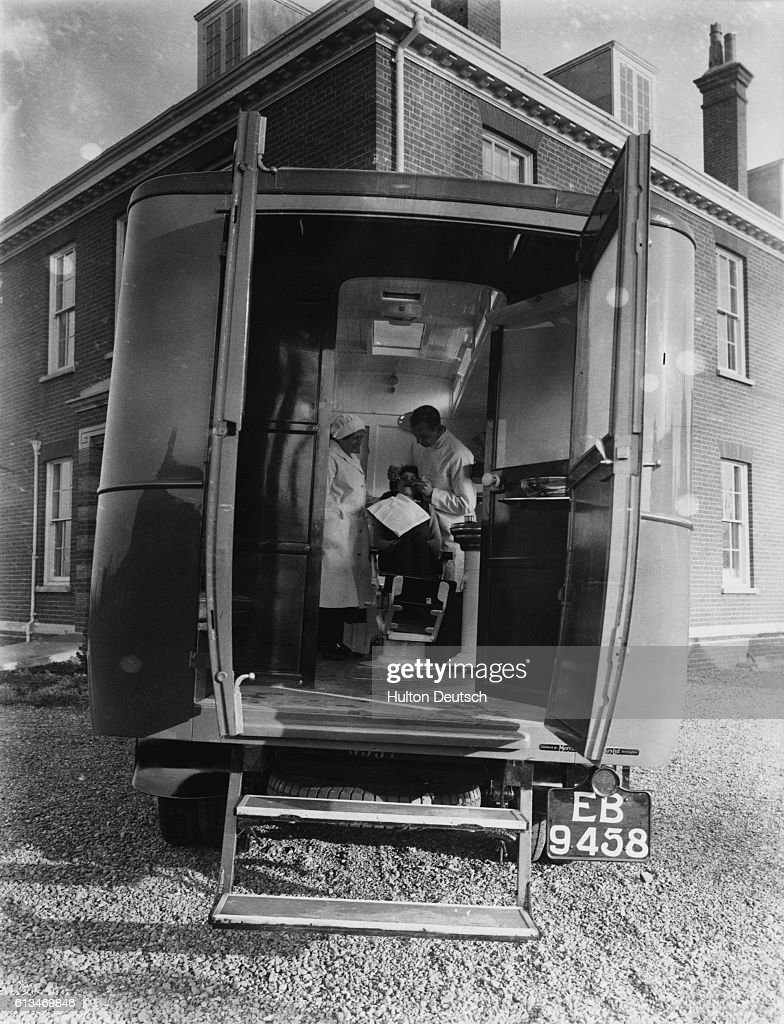 A dentist treats a patient inside the mobile dental clinic