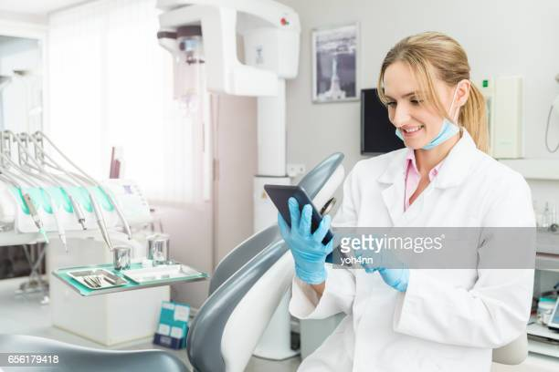 Dentist using digital tablet and ordering supplies