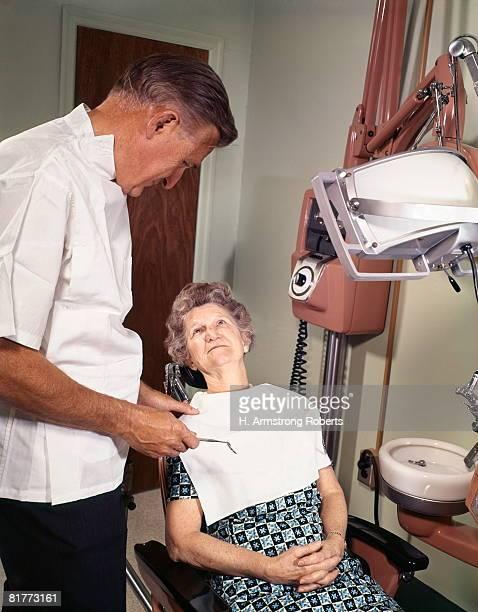 dentist visit elder woman patient speaking to dentist. - dentist 1950 stockfoto's en -beelden