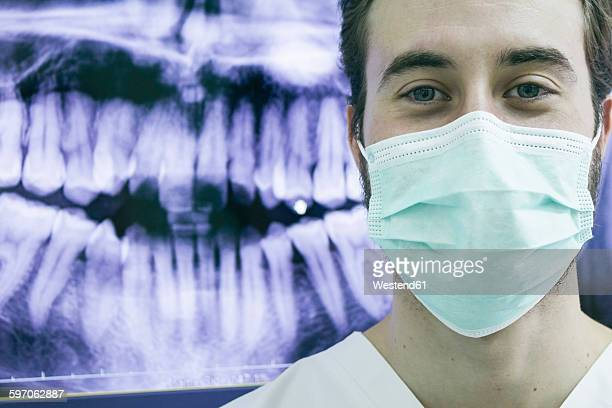 Dentist wearing a mask with an x-ray of teeth in background