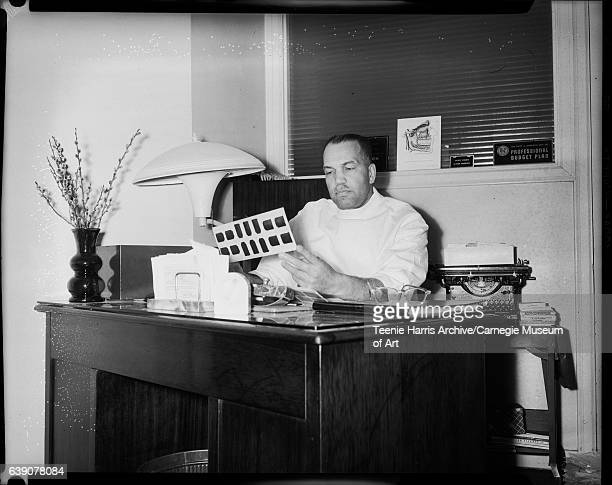 Dentist wearing light colored shirt holding xray of teeth and seated behind a desk in office with vase with flowers typewriter diagram of mouth and...