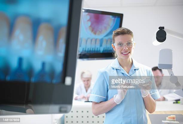 Dentist wearing safety glasses and holding dental equipment next to screen