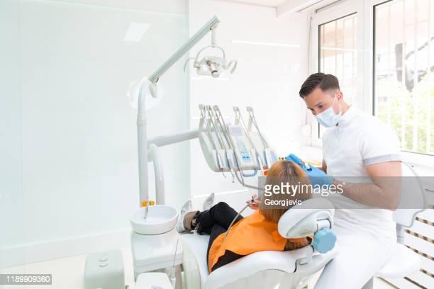 zahnarzt mit patient - zahnarzt stock-fotos und bilder
