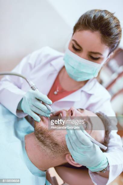 Dentist with Protective Mask and Gloves Doing Medical Control with a Dental Drill