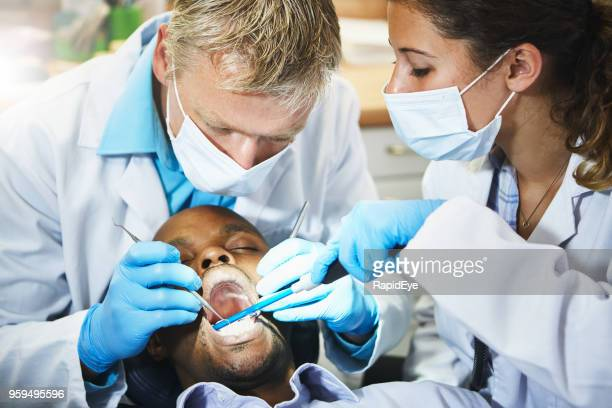 Dentist working on patient's teeth, assistant standing by