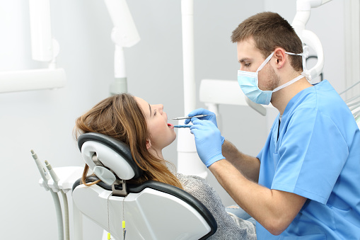 Dentist working with a patient 1055182908