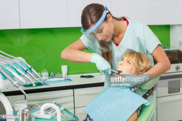 Dentistry. Dental examination. Blonde woman patient having a Dental Tooth Extraction Forceps. Dentist working, dentist office. Dental Health.