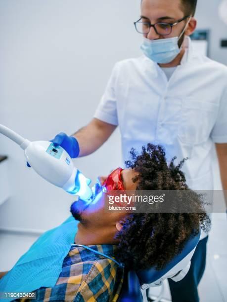 歯科歯科医は歯のホワイトニング歯科医療プロセスを働かせます - 漂白した ストックフォトと画像