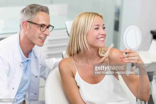 dentist's office for aesthetic cosmetic dentistry - mid adult dentist with short greying hair in white medical doctor's coat consulting female patient with long blonde hair on chair, doctor describing the bleaching whitening process with medical equipment - sorriso aperto foto e immagini stock