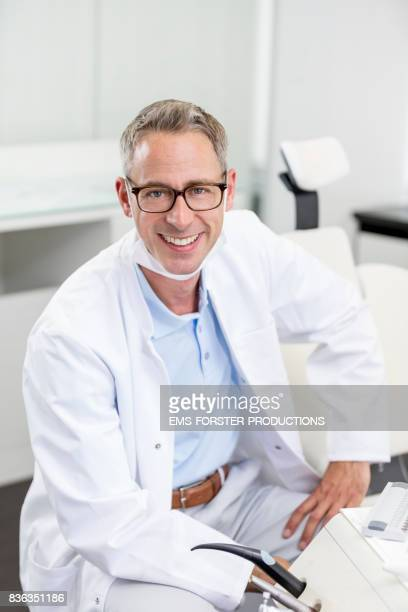 Dentist's office - mid adult dentist with short greying hair and a toothy smile in blue polo shirt and white medical scrubs doctor's coat