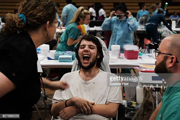 Dentists work on a patient at the Remote Area Medical mobile dental and medical clinic on December 3 2016 in Milton Florida It is expected that over...