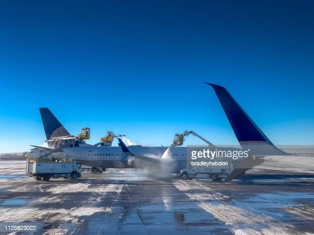 Denver airport ground staff de-ice the wings of United Airlines aircraft