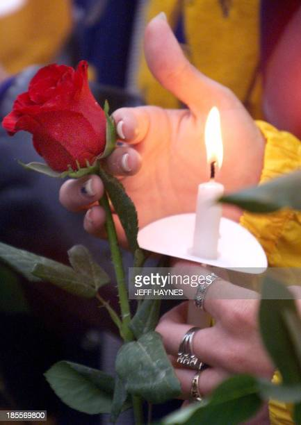 A Denver area resident holds a candle and a flower 21 April 1999 during a candle light vigil at Civic Center Park in Denver CO The vigil was held in...