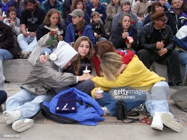Denver area residents comfort one another 21 April 1999 during a candle light vigil at Civic Center Park in Denver CO The vigil was held in honor of...