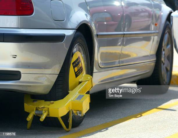 A 'Denver Boot' wheel lock is seen attached to a car in a parking lot August 1 2002 at Chicago's O'Hare International Airport Scofflaws with three...