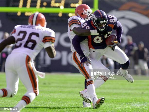 Denver Bronco Desmond Clark gets tackled by Cleveland Brown Persy Ellsworth after making a short reception 15 October 2000 at Mile High Stadium in...
