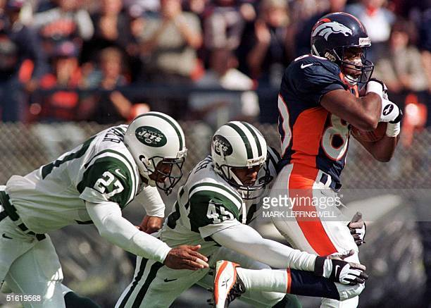 Denver Bronco Shannon Sharpe is dragged down from behind by the New York Jets Otis Smith and Steve Atwater at the Jets four yard line after Sharpe's...