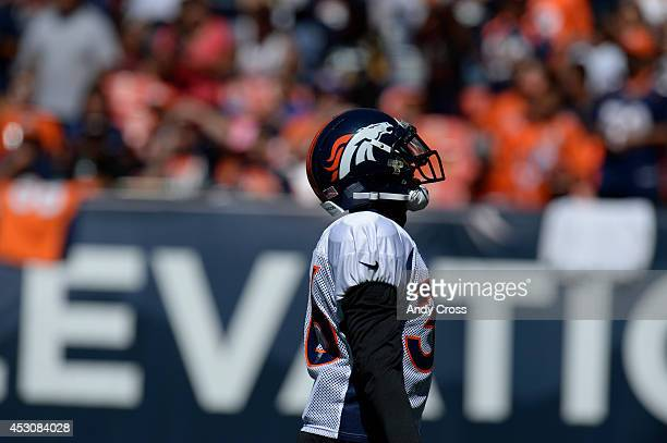 Denver Broncos CB Kayvon Webster pumps up the crowd entering the field for practice and scrimmage at Sports Authority Field at Mile High Saturday...