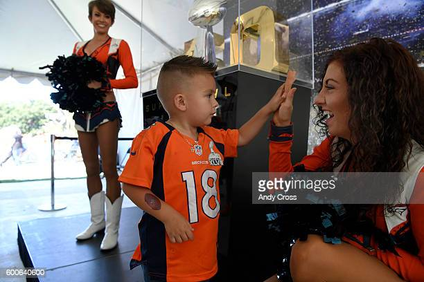 Denver Broncos cheerleader Gioia highfives young fan Jose Antonio in front Denver Broncos Super Bowl trophy at the NFL kickoff event at Civic Center...