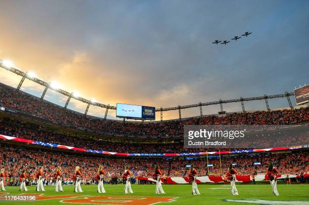 Denver Broncos cheerleaders stand during the performance of the national anthem as a group of A-10 fighter jets perform a flyover before a game...