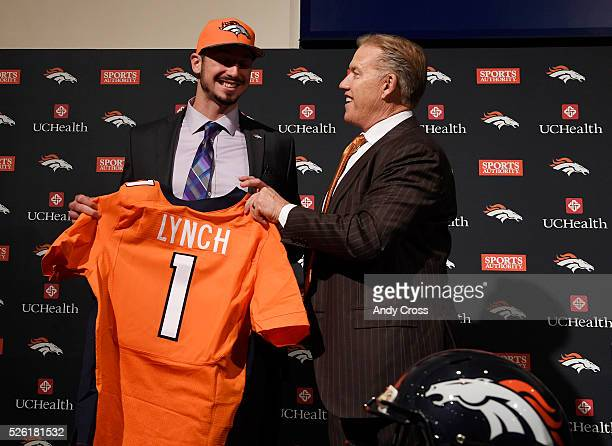 Denver Broncos executive vice president John Elway gives first round pick QB Paxton Lynch a jersey during Lynch's introductory press conference at...