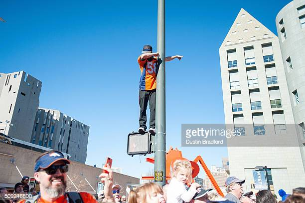 Denver Broncos fan performs a 'dab' wearing a Von Miller jersey as he watches from a light pole as Broncos players and personnel take part in a...