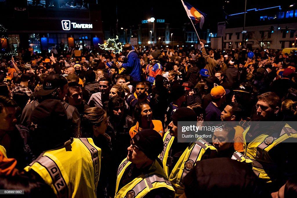 Denver Broncos fans celebrate in the street as Denver police officers walk through the crowd after the Denver Broncos won Super Bowl 50 on Market Street in Lower Downtown on February 7, 2016 in Denver, Colorado.