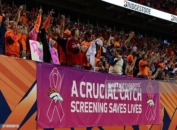 Denver Broncos fans cheer near a sign for the NFL's breast cancer awareness campaign during a game between the Denver Broncos and the Houston Texans...