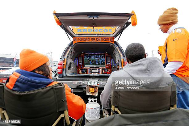 Denver Broncos fans watch football on a TV in the back of their car as they have a tail gate party outside of the venue before a 2015 AFC Divisional...
