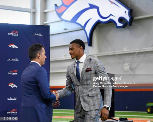 Denver Broncos first round draft pick, Patrick Surtain II, right, shakes hands with Broncos GM George Paton before taking the podium for his...
