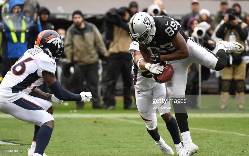 Denver Broncos free safety Bradley Roby (29) knocks the ball away from Oakland Raiders wide receiver Amari Cooper (89) as Denver Broncos free safety Darian Stewart (26) comes in on a late hit knocking Cooper out of the game with a concussion during the second quarter on November 26, 2017 in Oakland, CA at Oakland-Alameda County Stadium.