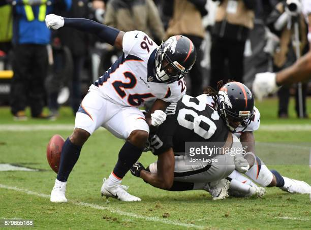 Denver Broncos free safety Bradley Roby knocks the ball away from Oakland Raiders wide receiver Amari Cooper as Denver Broncos free safety Darian...