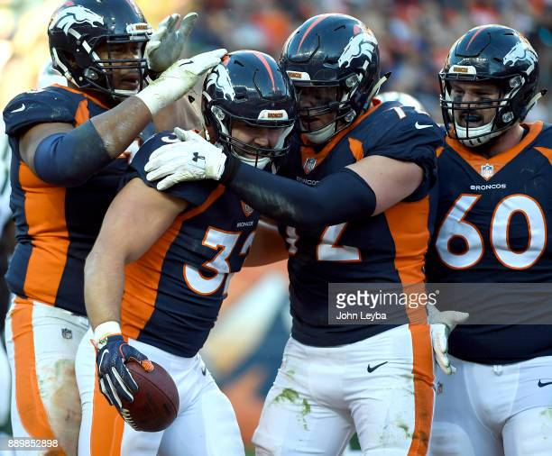 Denver Broncos fullback Andy Janovich celebrates his touchdown with offensive guard Max Garcia and offensive tackle Garett Bolles during the third...