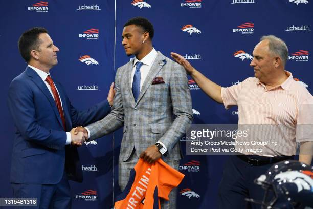 Denver Broncos GM George Paton, left, shakes hands with Denver Broncos first round draft pick, Patrick Surtain II, center, as head coach Vic Fangio,...