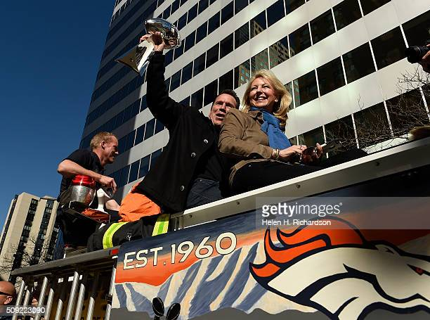 Denver Broncos head coach Gary Kubiak sits with his wife Rhonda while he holds the Lombardi trophy over his head as they ride atop a Denver Fire...