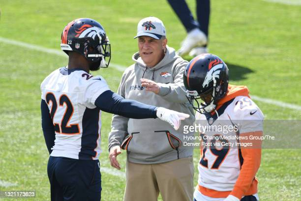 Denver Broncos head coach Vic Fangio, center, talks to safety Kareem Jackson , left, by cornerback Bryce Callahan during the team practice at...
