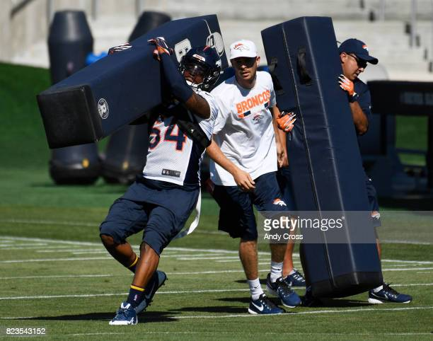 Denver Broncos inside linebacker Brandon Marshall grabs a tackle dummy on the first day of training camp at Dove Valley July 26 2017