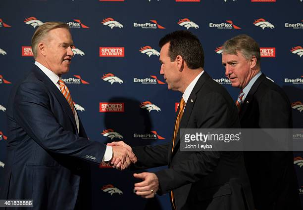 Denver Broncos John Elway General Manager and Executive Vice President of Football Operations shakes hands with Head Coach Gary Kubiak as Joe Ellis...