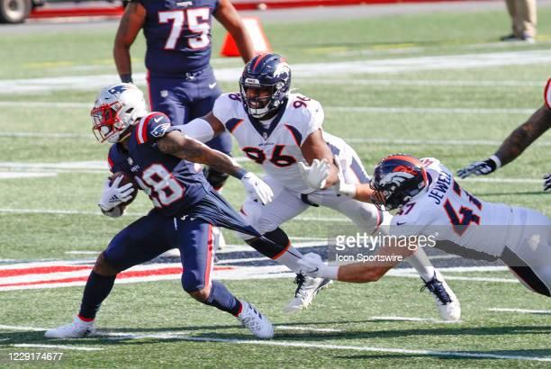 Denver Broncos linebacker Josey Jewell hangs onto New England Patriots running back James White during a game between the New England Patriots and...