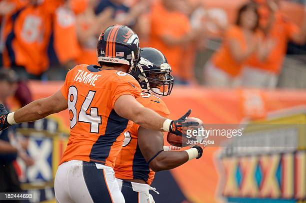 Denver Broncos linebacker Steven Johnson is congratulated by Denver Broncos tight end Jacob Tamme after blocking a punt and returning it for a...