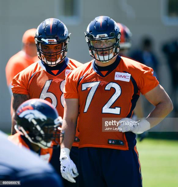 Denver Broncos linebacker Vontarrius Dora and offensive tackle Garett Bolles watch drills during practice at mandatory mini camp on June 14 2017 in...