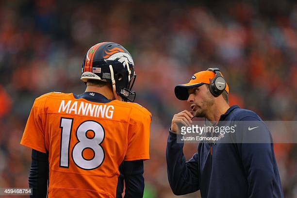 Denver Broncos offensive coordinator Adam Gase has a word with Quarterback Peyton Manning during a game at Sports Authority Field at Mile High on...