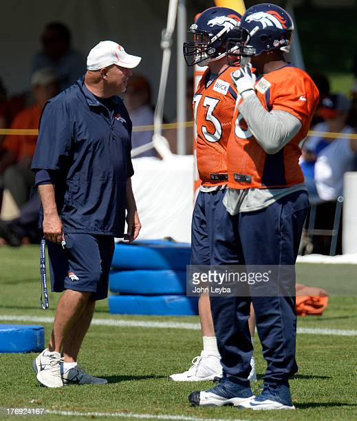 Denver Broncos offensive line coach Dave Magazu talks with Denver Broncos guard Chris Kuper and Denver Broncos tackle Ryan Clady during practice...