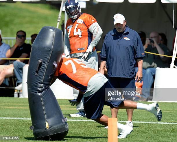Denver Broncos offensive line coach Dave Magazu watches Denver Broncos tackle Chris Clark hit the blocking dummy during practice August 19 2013 at...